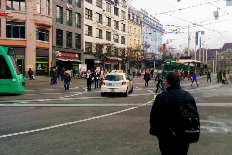 Fussgänger, Trams, Taxi, Velofahrerin und Gleisgewirr