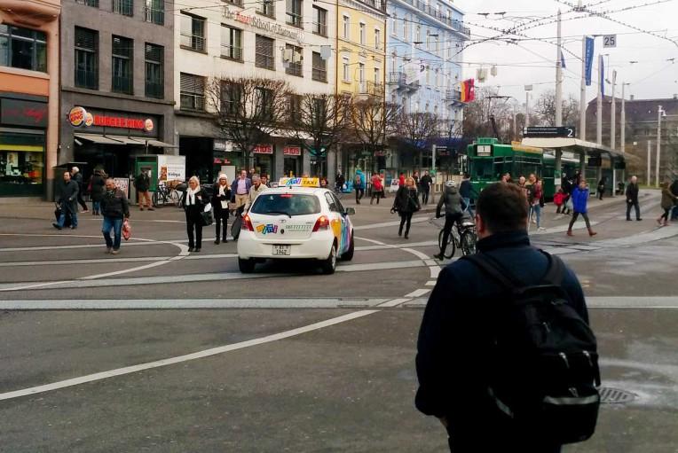 Durcheinander von Fussgängern, einem Taxi, einem Velo und einem Tram