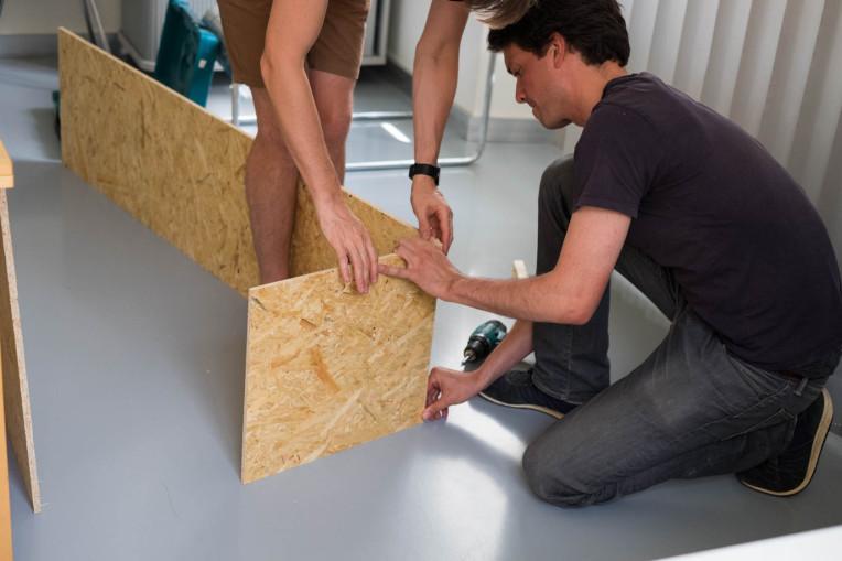 Holzplatten werden von Hand gehalten