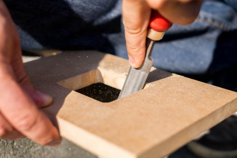 Loch in Holzplatte wird mit einer Feile vergrössert