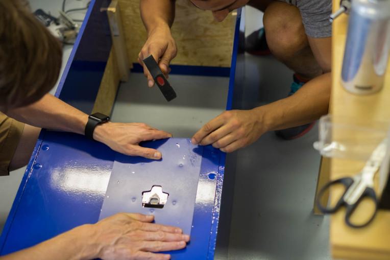 Zwei Männer montieren einen Belegdrucker im Automat.