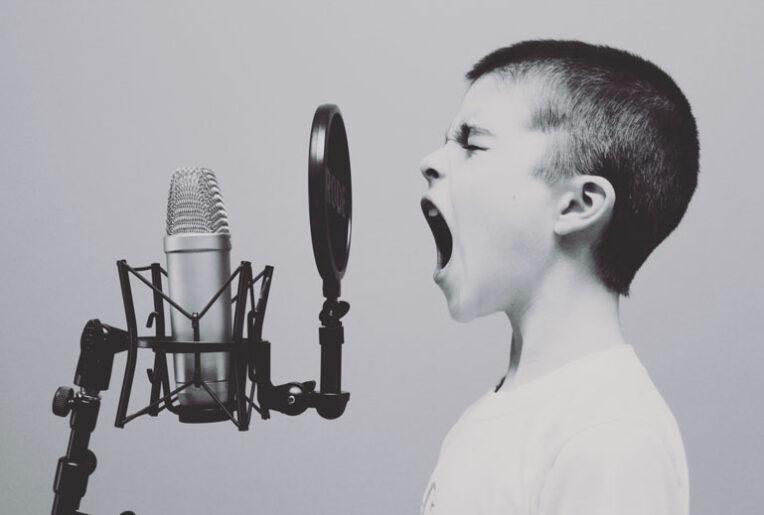 Junge singt in ein Mikrofon. Sprachsteuerung / Voice first mit Alexa, Google Assitant, Siri, Cortana & Co.