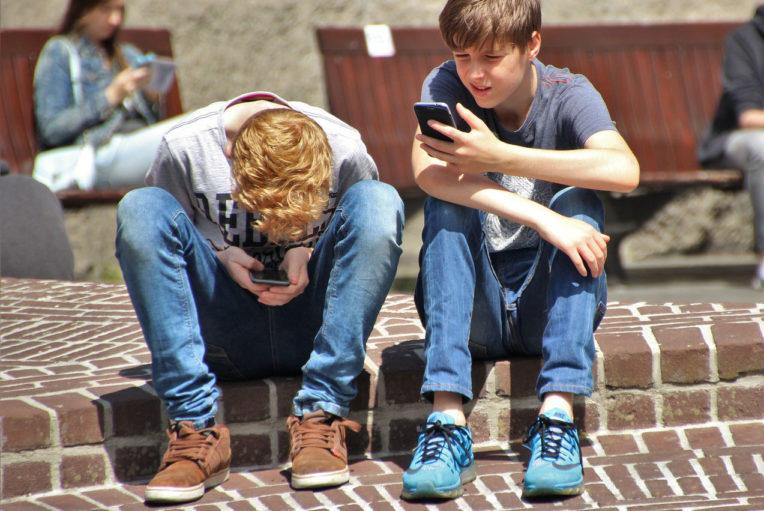 Zwei Knaben schauen auf ihr Smartphone. Sie halten dieses sehr nahe vor ihren Augen.