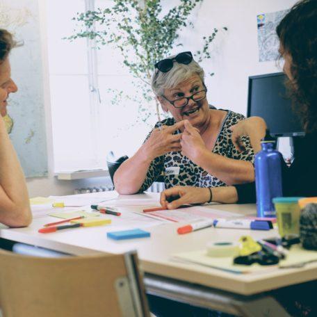 3 Personen, die an einem Tisch diskutieren.