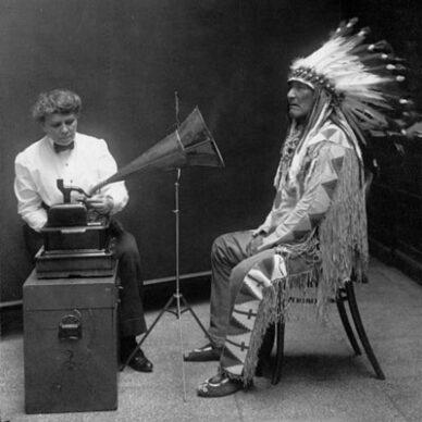 Ein Piegan Indianer hört sich 1916 eine Aufnahme an – das Zeitalter der Tondatenträger hat begonnen. Sprachsteuerung / Voice first mit Alexa, Google Assitant, Siri, Cortana & Co.