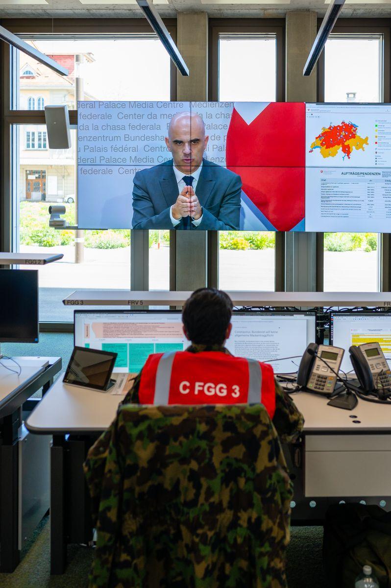 Mitarbeiter der Alarmzentrale verfolgt eine Medienkonferenz auf dem zentralen Bildschirm.